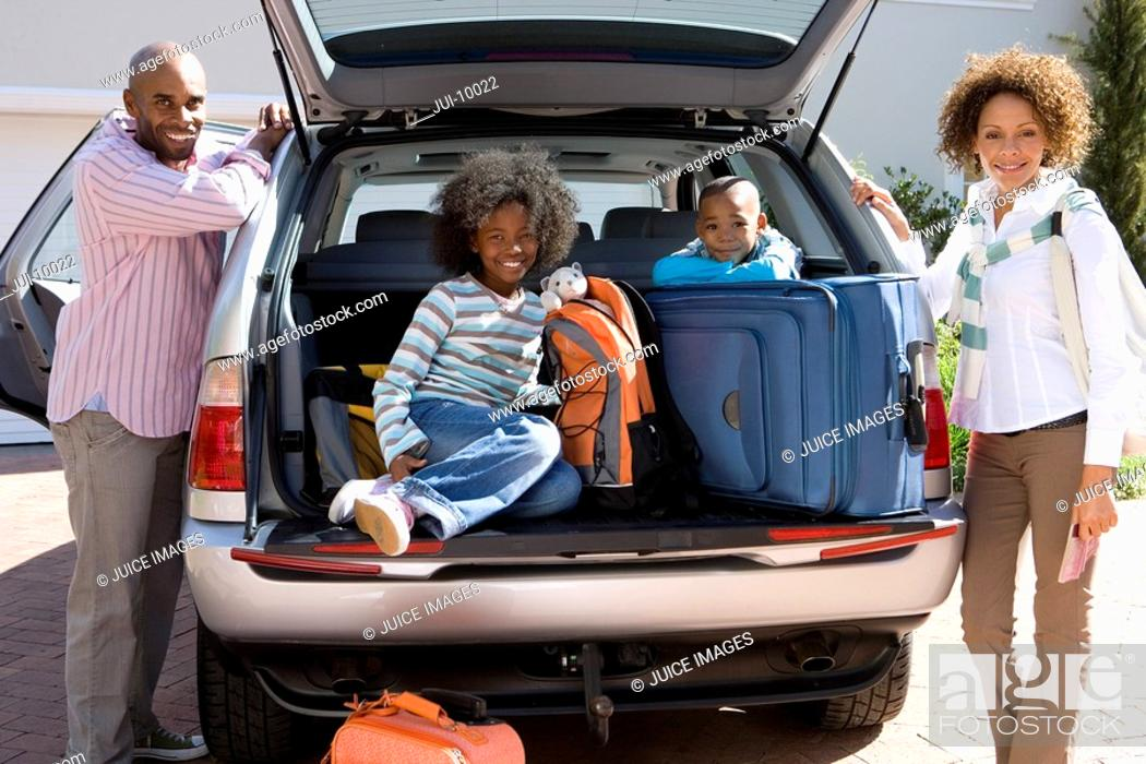 Stock Photo: Man and woman by son and daughter 6-10 in back of car with luggage, smiling, portrait.