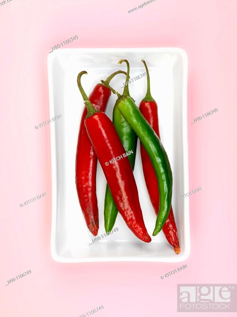 Stock Photo: Chilli Peppers isolated on a pink background.