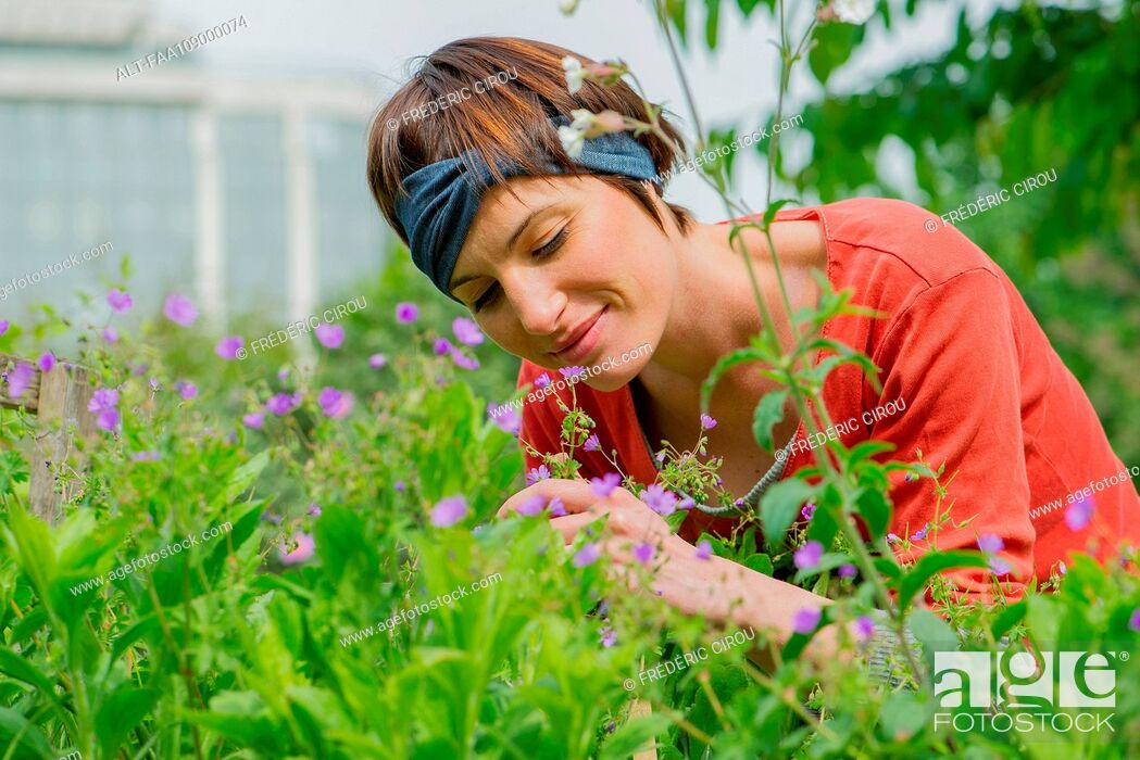 Stock Photo: Woman smelling flowers in garden.