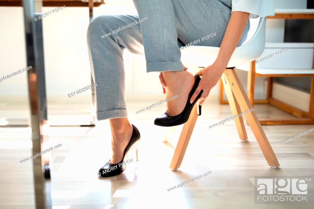 Stock Photo: Young Businesswoman Suffering From Leg Pain Because Of Uncomfortable Shoes In Office.