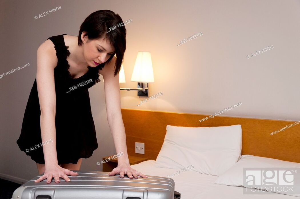 Stock Photo: Woman packing suitcase in hotel room.