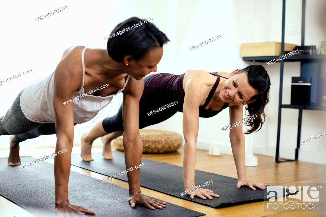 Stock Photo: Two women doing gymnastics at home.