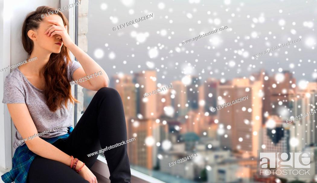 Photo de stock: people, emotion, winter, christmas and teens concept - sad unhappy pretty teenage girl sitting at window over city background and snow.