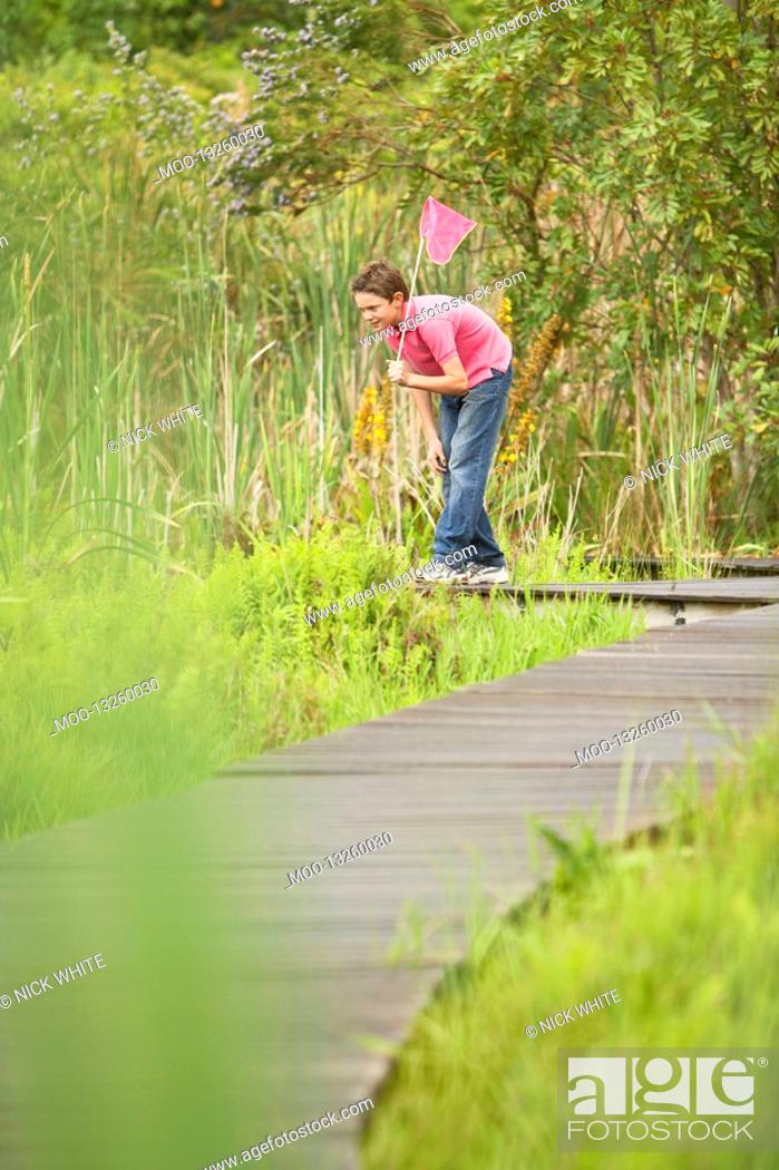 Stock Photo: Boy Looking for Wildlife in Marsh.