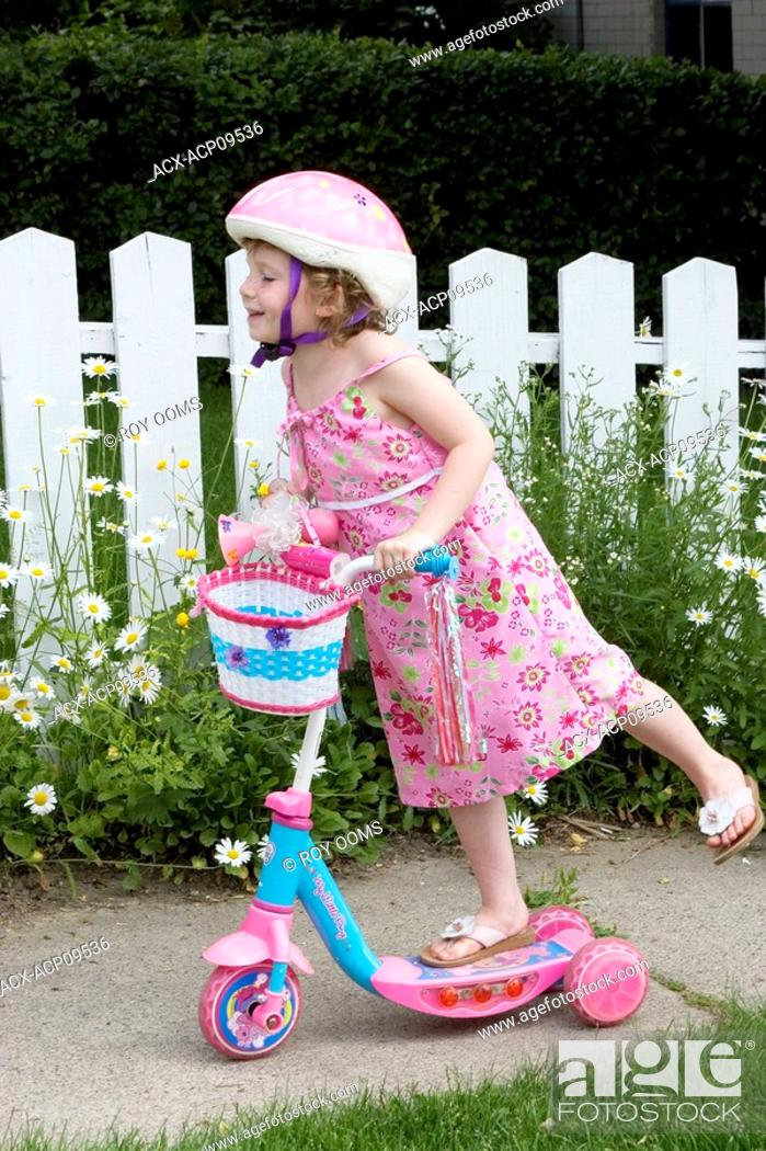 9003a21f76390 Stock Photo - 5 year old girl with sundress and hat riding in front of  picket fence with scooter