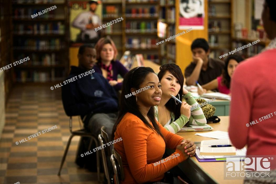Stock Photo: Teacher talking to teenage students in library.