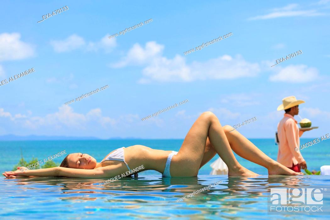 Imagen: woman lying at the surface of a swimming pool, relaxing.