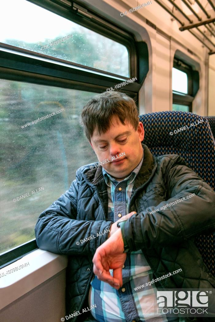 Stock Photo: Man with down syndrome checking time on train.
