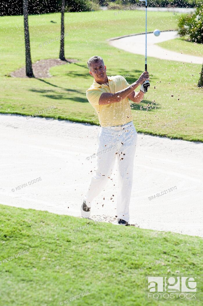 Stock Photo: Caucasian man golfing from sand trap on golf course.