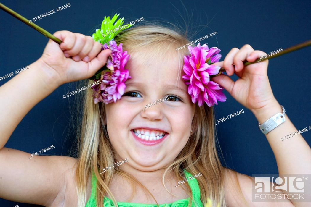 Stock Photo: silly little girl playing with flowers.