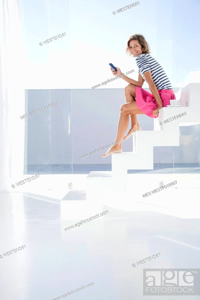 Stock Photo: Spain, Mid adult woman sitting on stairway with cell phone.