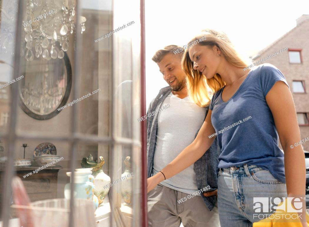 Stock Photo: Belgium, Tongeren, happy young couple looking in shop window of an antique shop.