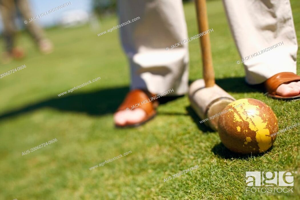 Stock Photo: Low section view of a person with a ball and a croquet mallet.