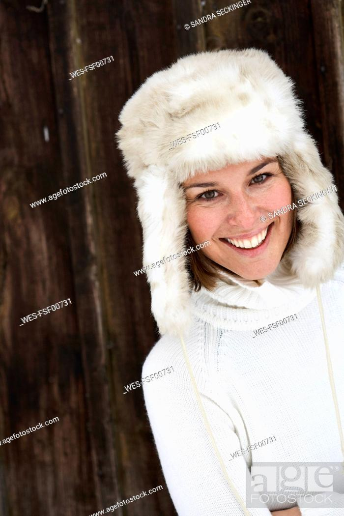 Stock Photo: Portrait of smiling woman wearing fur cap in winter.