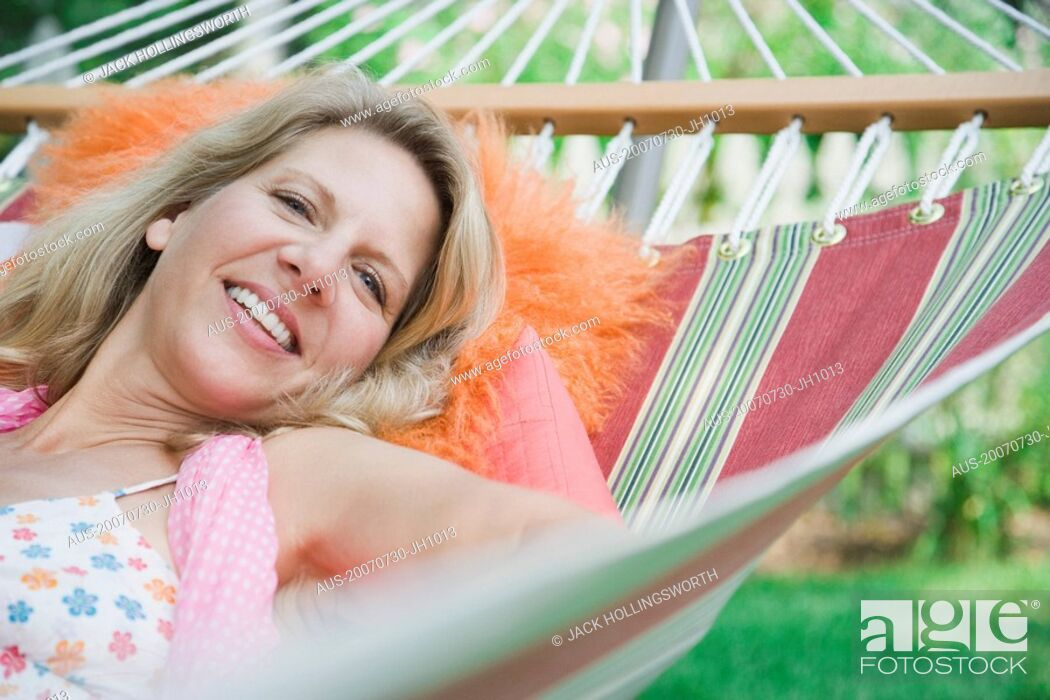 Stock Photo: Portrait of a mature woman lying in a hammock and smiling.