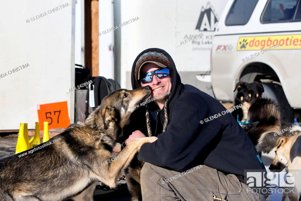 Stock Photo: Matt Failor #57 gets some love and kisses from one of his dogs before the 2014 Iditarod restart in Willow, Alaska.