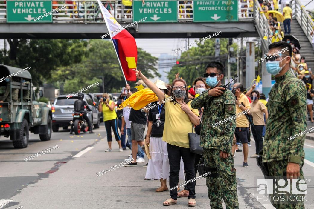 Stock Photo: Supporters gather beside the motorcade of former Philippine President Benigno Aquino III before his burial in Quezon City, Philippines.