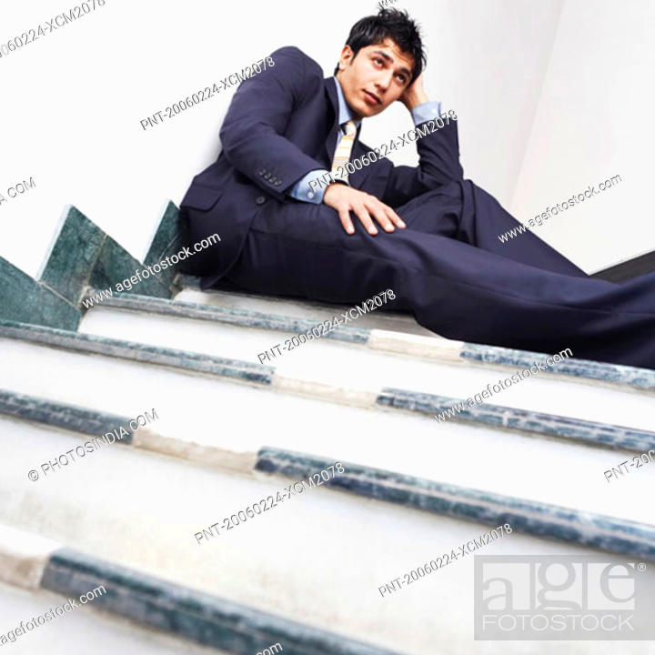 Stock Photo: Low angle view of a businessman sitting on the staircase.