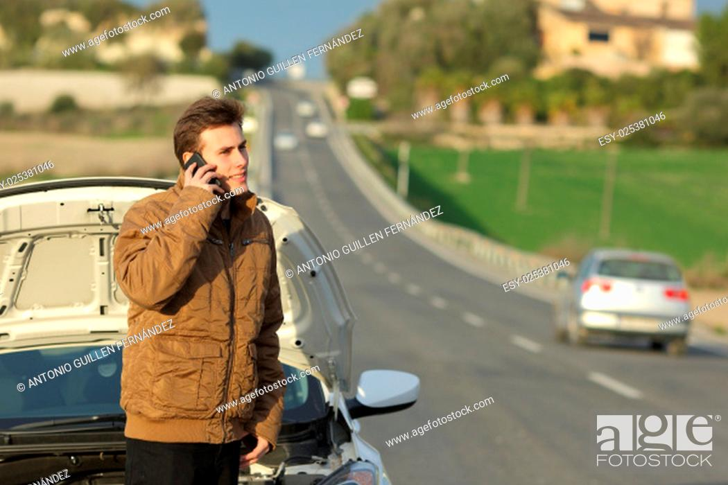 Stock Photo: Happy man calling roadside assistance for his breakdown car in a country road.