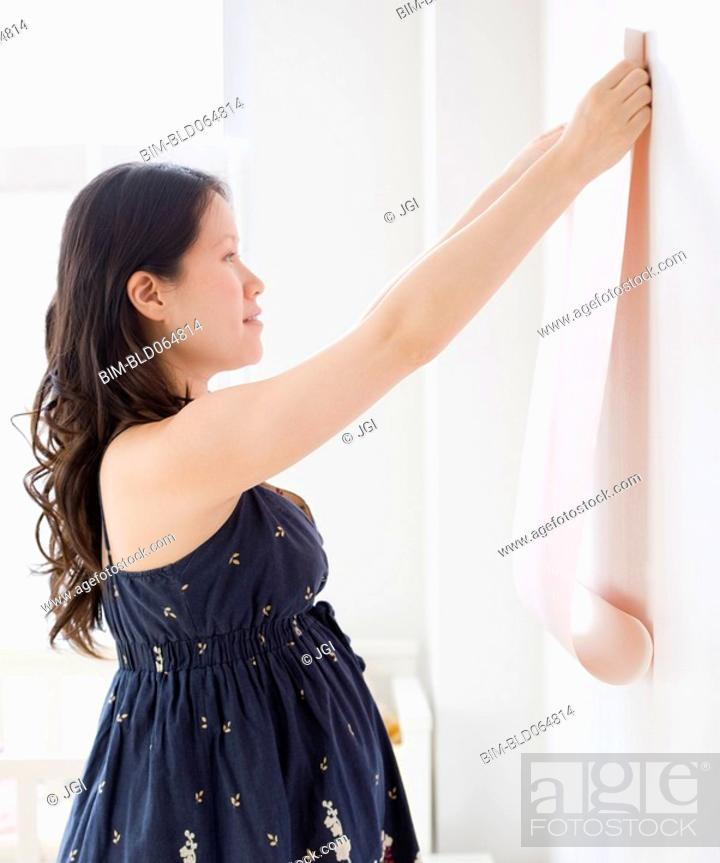 Stock Photo: Pregnant Asian woman decorating room with wallpaper.