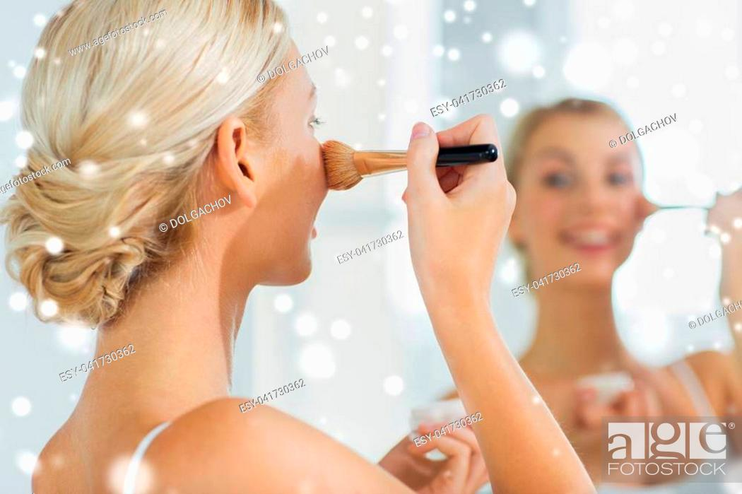 Stock Photo: beauty, make up, cosmetics, morning and people concept - close up of smiling young woman makeup brush and powder foundation looking to mirror at home bathroom.