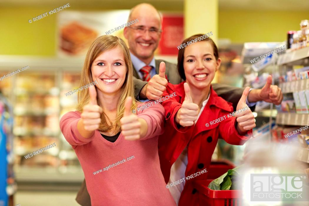 Stock Photo: Germany, Cologne, Man and women showing thumbs up in supermarket.