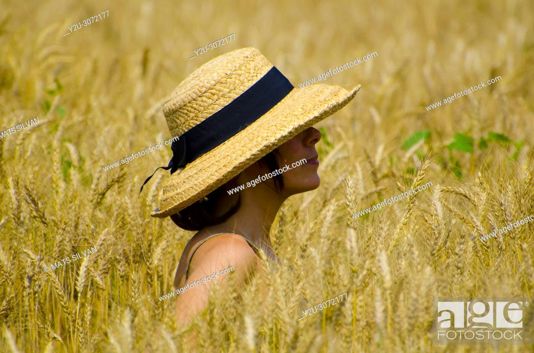Stock Photo: Woman with a Straw Hat Standing in a Wheat Field in Locarno, Switzerland.