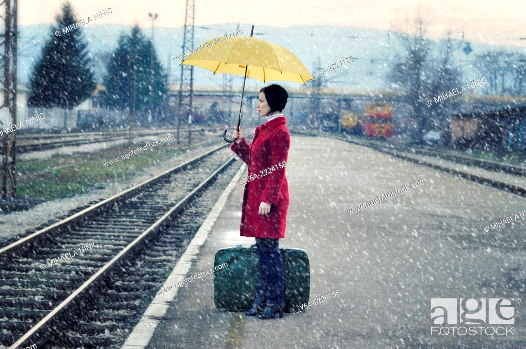 Stock Photo: Mid adult woman standing on railroad station platform with suitcase holding umbrella.