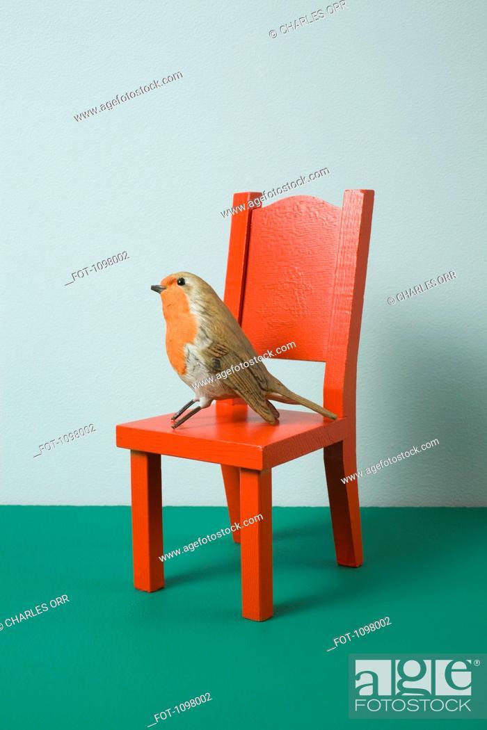 Stock Photo: An imitation bird sitting on a miniature chair.