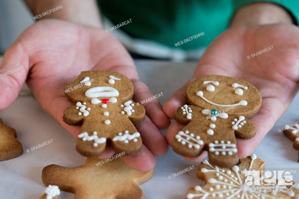 Stock Photo: Man's hands holding two different Gingerbread Men, close-up.