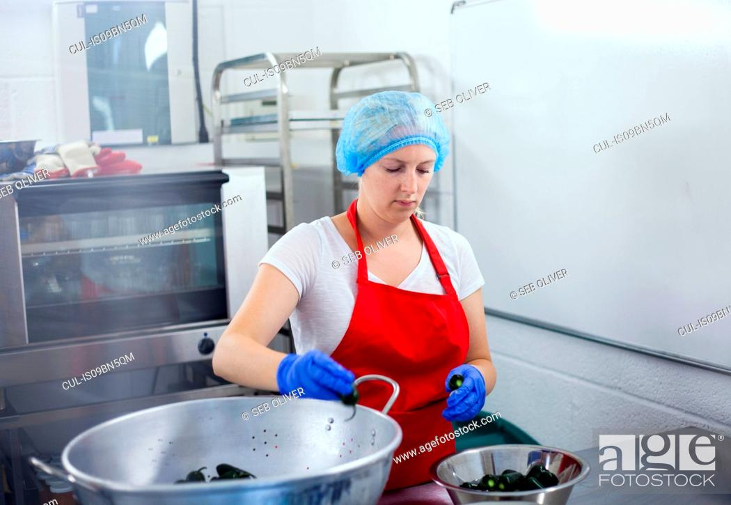 Stock Photo: Woman preparing chillies to make jam in industrial kitchen.