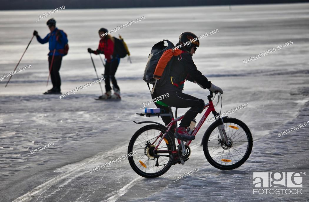Stock Photo: Cyclist and two long distance ice skaters on Lake Malaren during Sigtunarannet Vikingarannet 2019, Sigtuna, Sweden, Scandinavia.