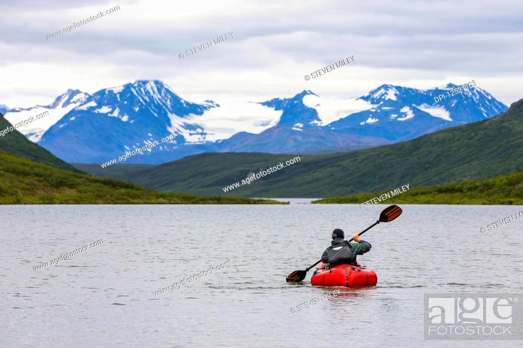 Photo de stock: A man paddles a packraft across Landmark Gap Lake with the Alaska Range in the distance; Alaska, United States of America.