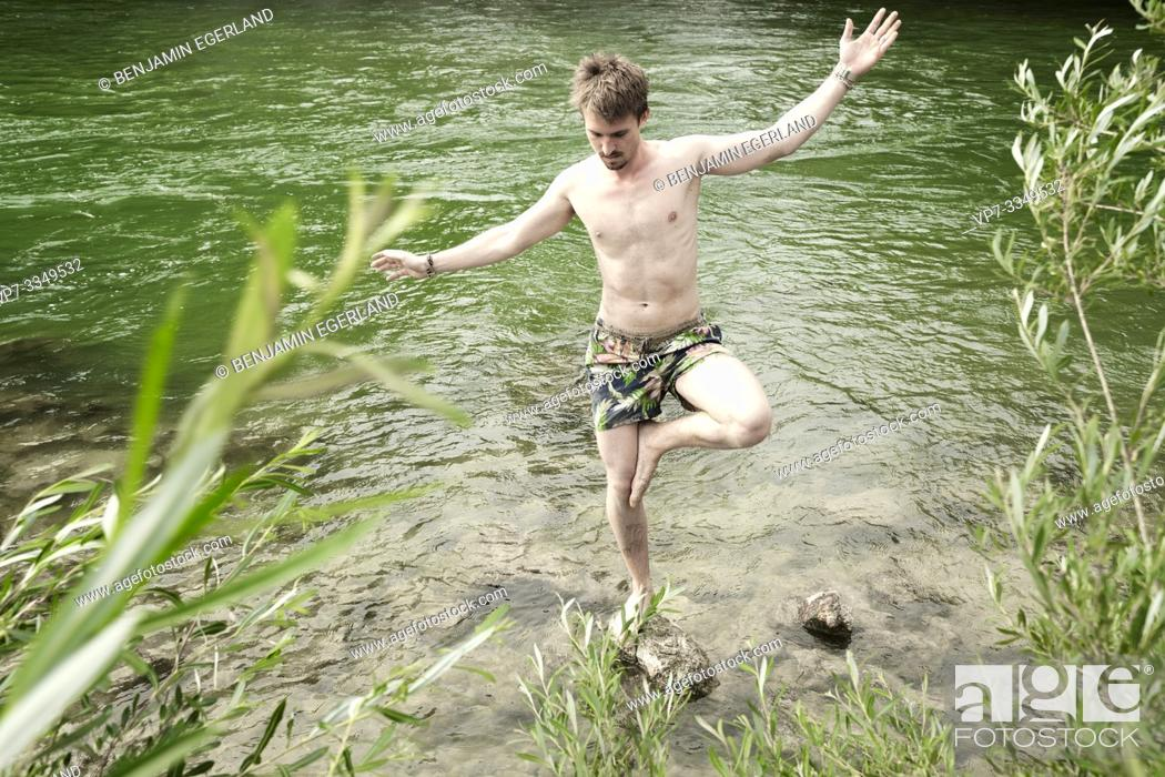 Photo de stock: man balancing on stone in river Isar, in Munich, Germany.