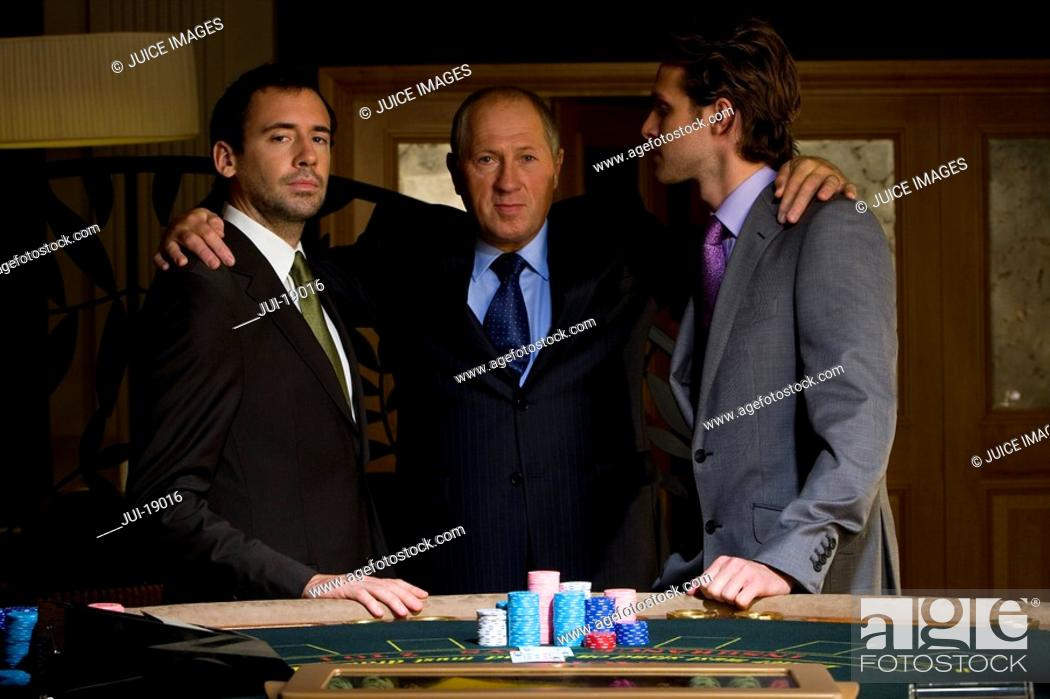 Stock Photo: Mature man with arms around young men by poker table, portrait.