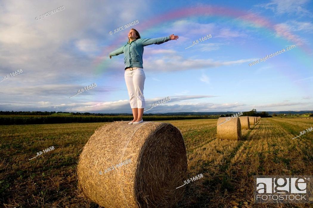 Stock Photo: Girl standing in hay bale.
