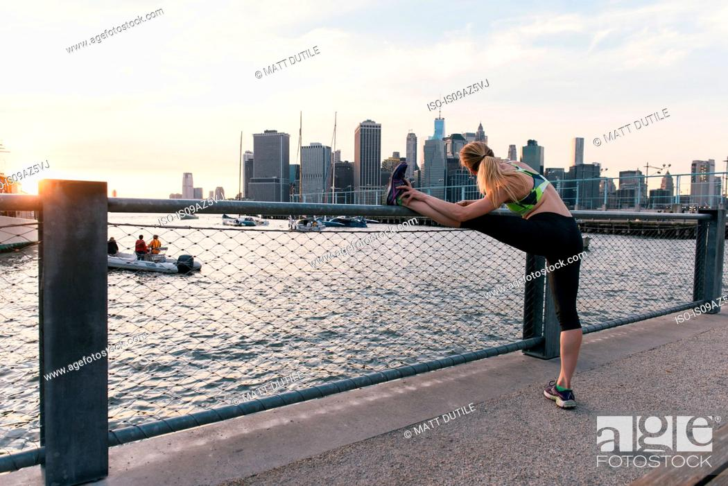 Stock Photo: Young woman exercising outdoors, at waterfront, stretching leg, rear view, Brooklyn, New York, USA.