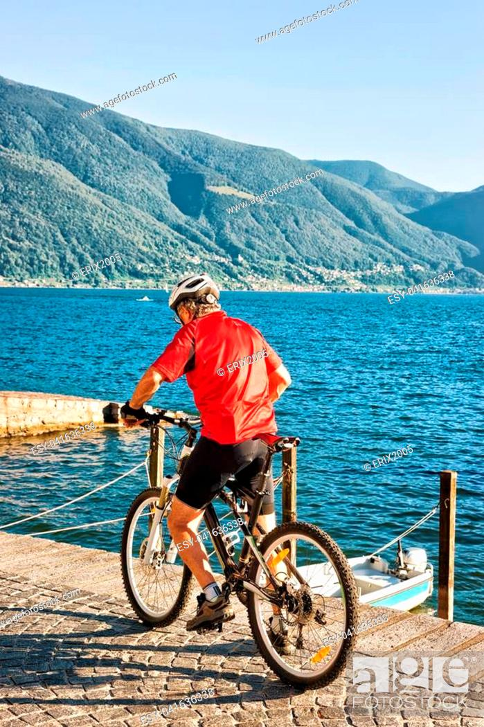 Stock Photo: Man riding a bicycle at the promenade at the luxurious resort in Ascona on Lake Maggiore, Ticino canton in Switzerland.