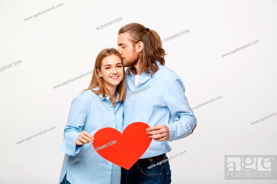 Stock Photo: Portrait of young happy couple in love holding red paper heart.