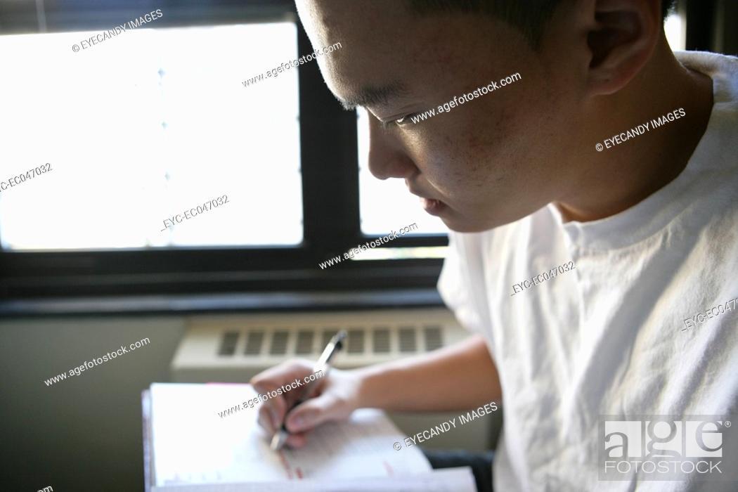 Stock Photo: Teenage boy 15-17 writing in book.