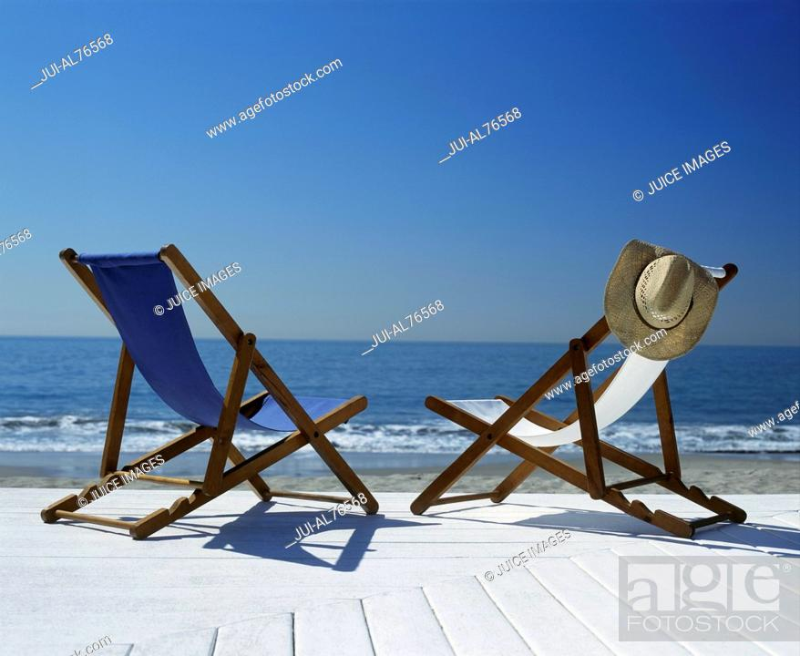 Stock Photo: View of two lawn chairs on a deck overlooking the beach.