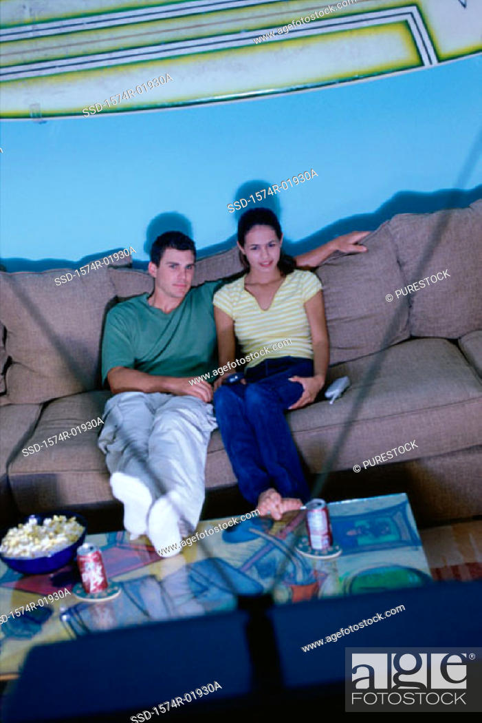 Stock Photo: High angle view of a couple sitting on a couch and watching television.