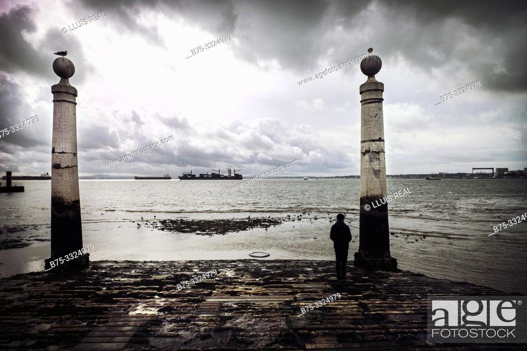 Stock Photo: A man looking at the sea Cais das Colunas, Plaza del Comercio, Lisbon, Europe.