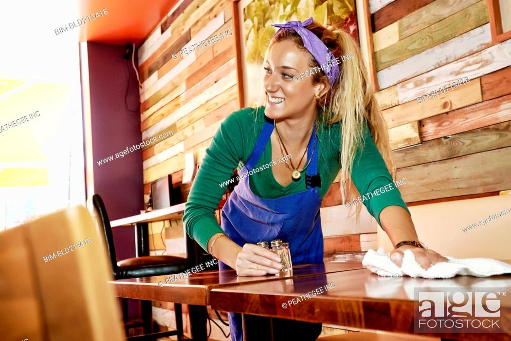 Stock Photo Caucasian Server Wiping Down Tables In Cafe