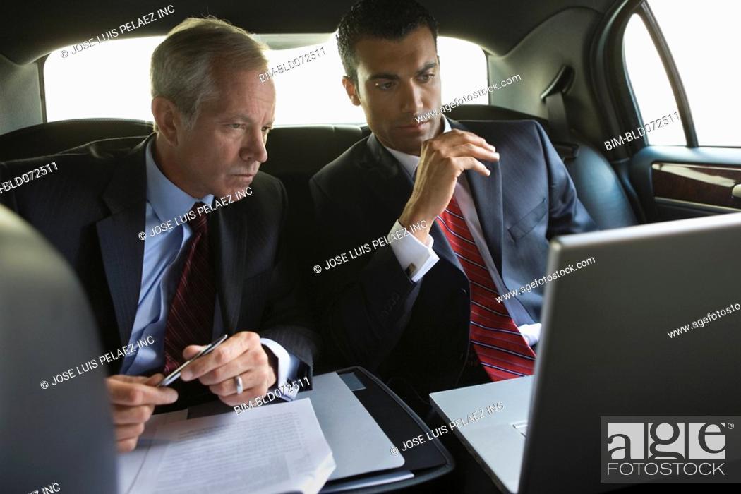 Stock Photo: Businessmen using laptop in limousine.