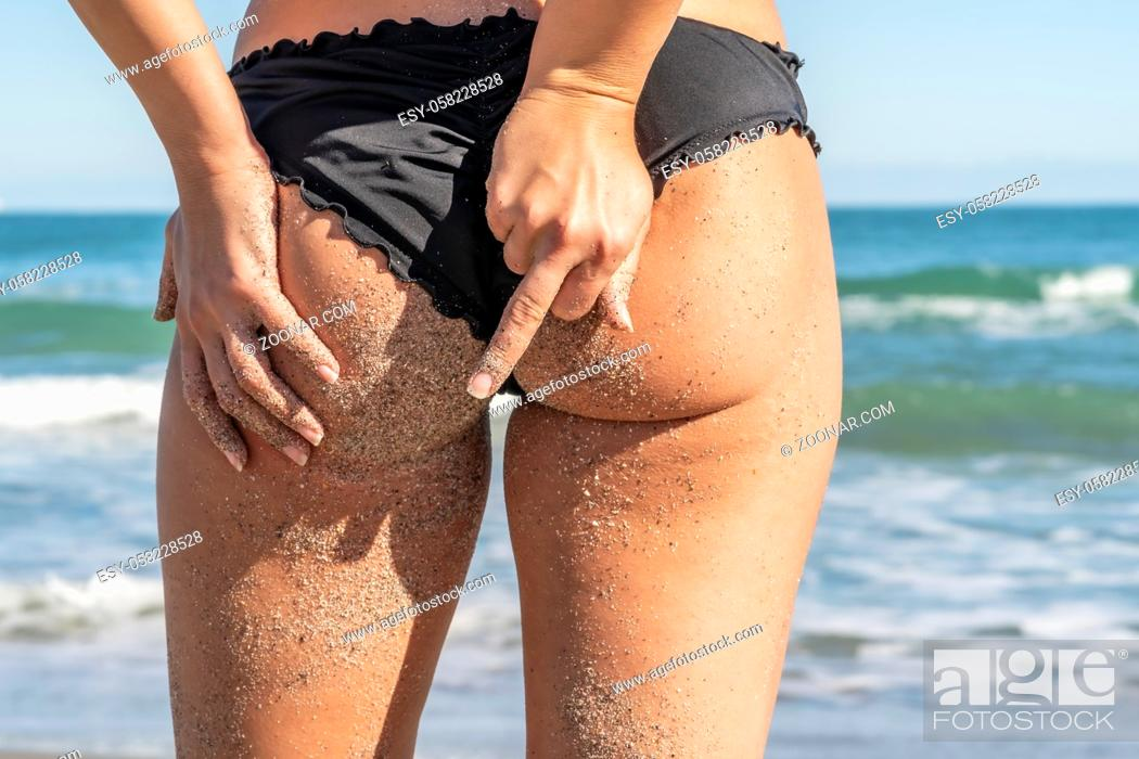 Stock Photo: A gorgeous bikini model posing in a beach environment.