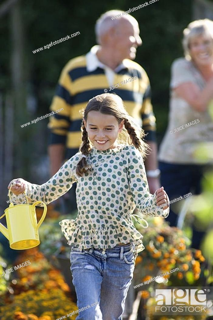 Stock Photo: Girl 8-10 running in garden, holding watering can, smiling, grandparents standing in background.