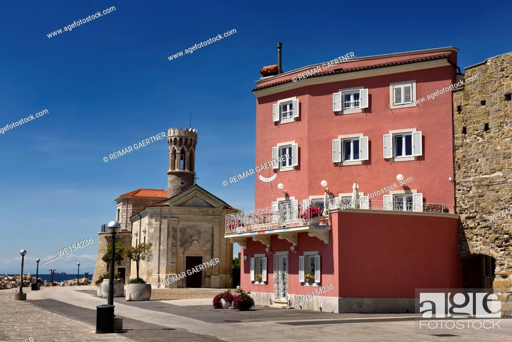 Stock Photo: Red stucco apartment on the Adriatic Sea coast at Piran Slovenia next to the Punta lighthouse and 13th century Church of St Clement.