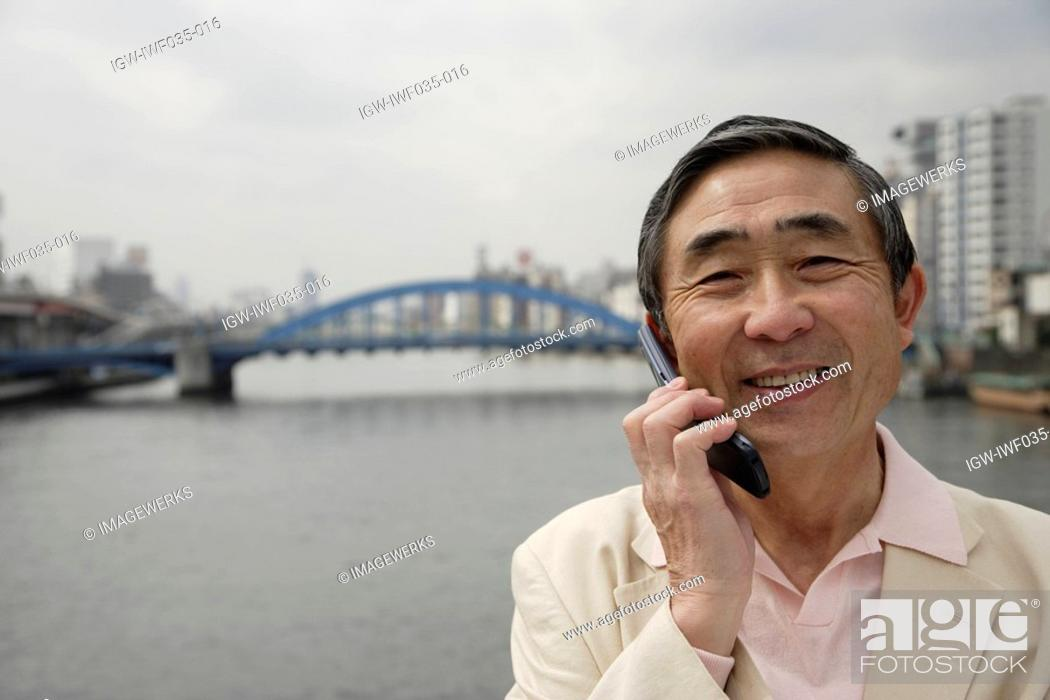 Stock Photo: Portrait of a senior man using mobile phone.