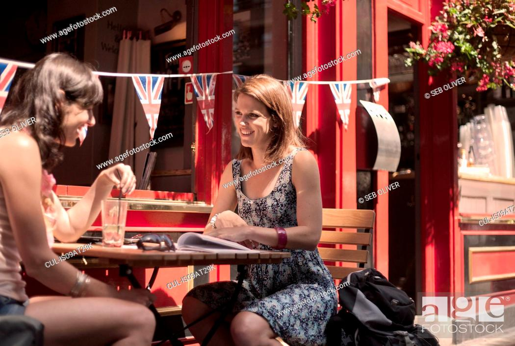 Stock Photo: Two women friends guidebook planning outside traditional pub, London UK.